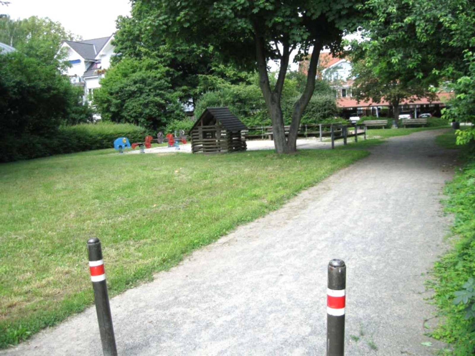 Holzhaus, Sandkasten und Wippen auf dem Spielplatz Rischweg