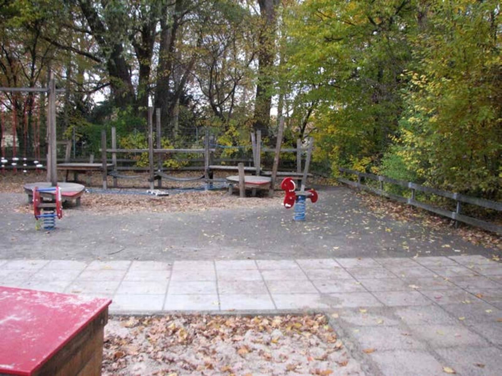 Spielgeräte aus Holz und Wipptiere auf dem Spielplatz Tegelweg