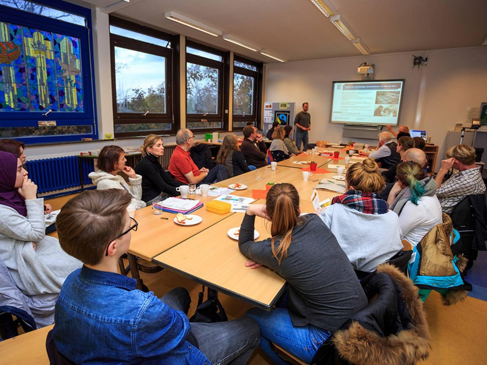 Schülerinnen, Schüler und Lehrkräfte sitzen um einen langen Tisch und hören einem Vortrag zu