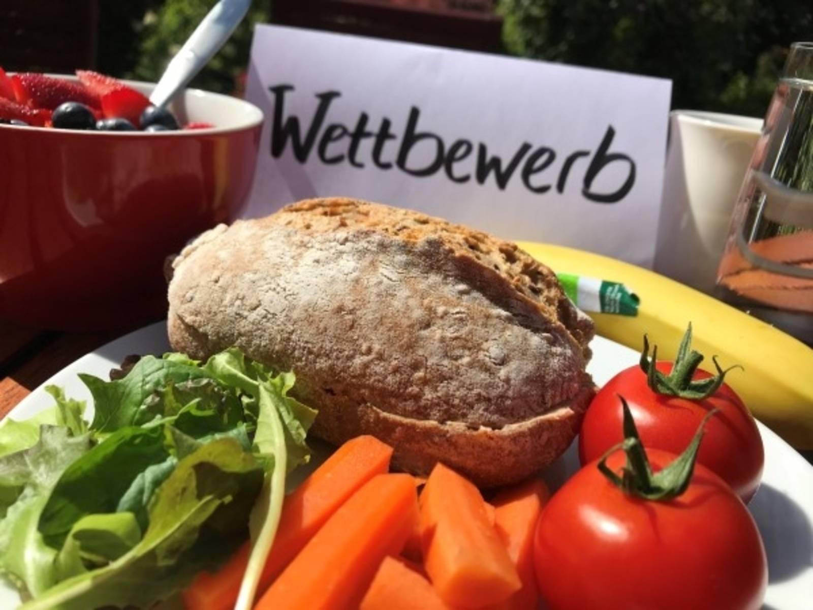 """Ein Teller mit Brötchen und Gemüse vor einem Schild mit der Aufschrift """"Wettbewerb"""""""