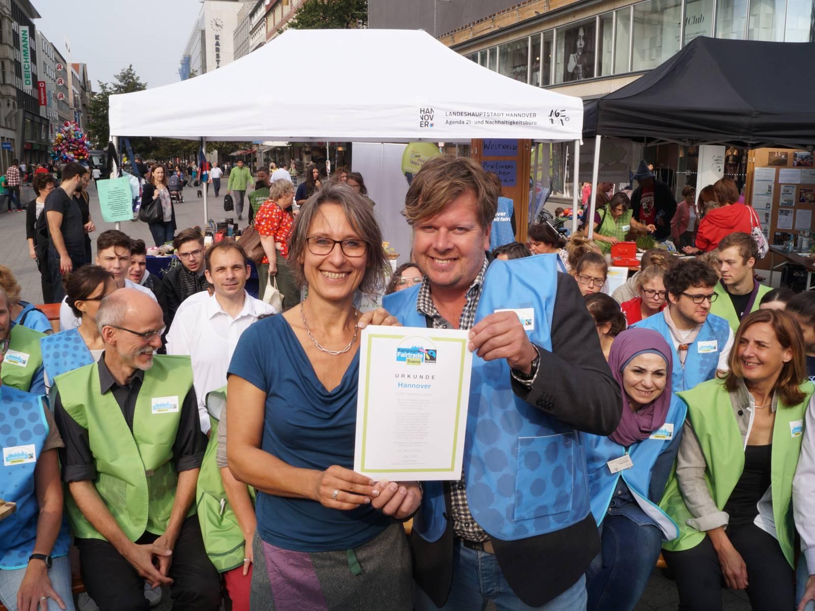 Susanne Wildermann vom Agenda21- und Nachhaltigkeitsbüro und Carsten Elkmann von TransFair e.V.  präsentieren vor Aktiven am Kröpke die Fair Trade Town Urkunde für Hannover