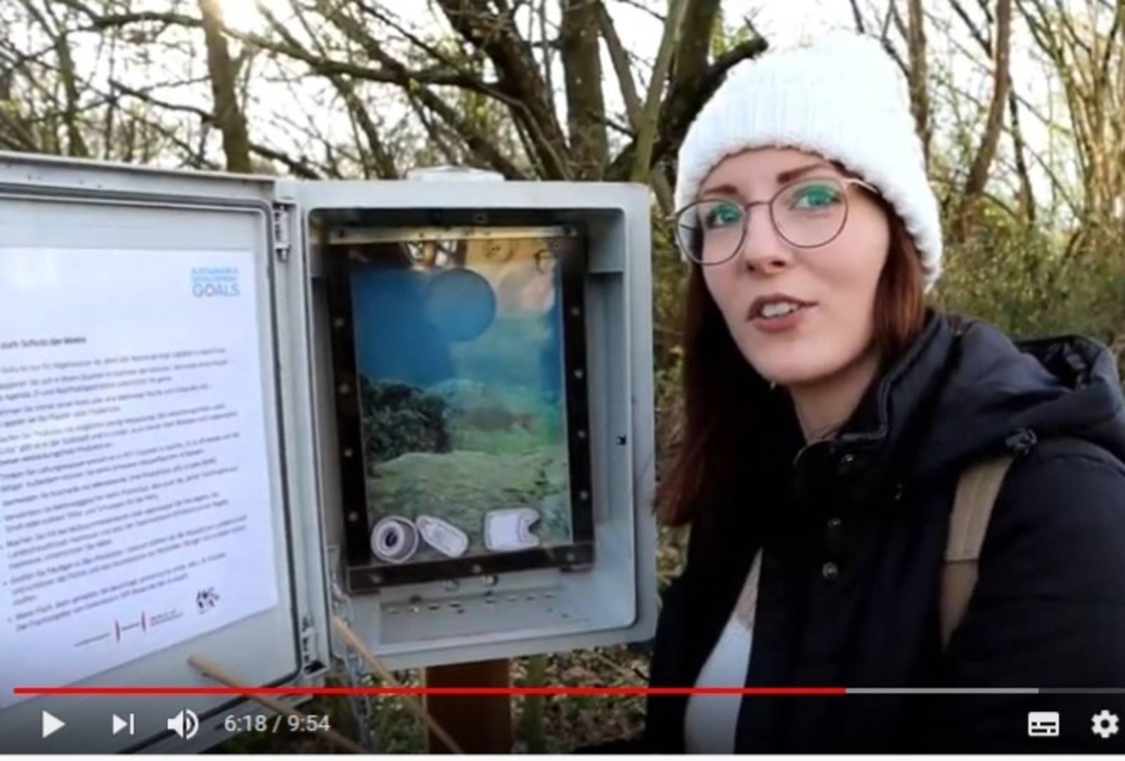 """Eine junge Frau steht vor einem geöffneten Cache zum Thema """"Leben im Wasser"""""""