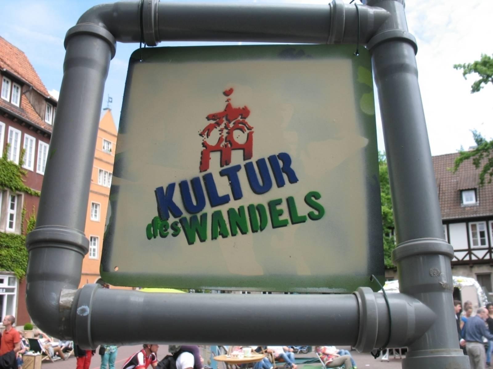"""Schild aus zusammengesetzten Plastikrohren und -winkeln, das im Inneren auf einer kleinen Tafel die Aufschrift """"Kultur des Wandels"""" trägt"""