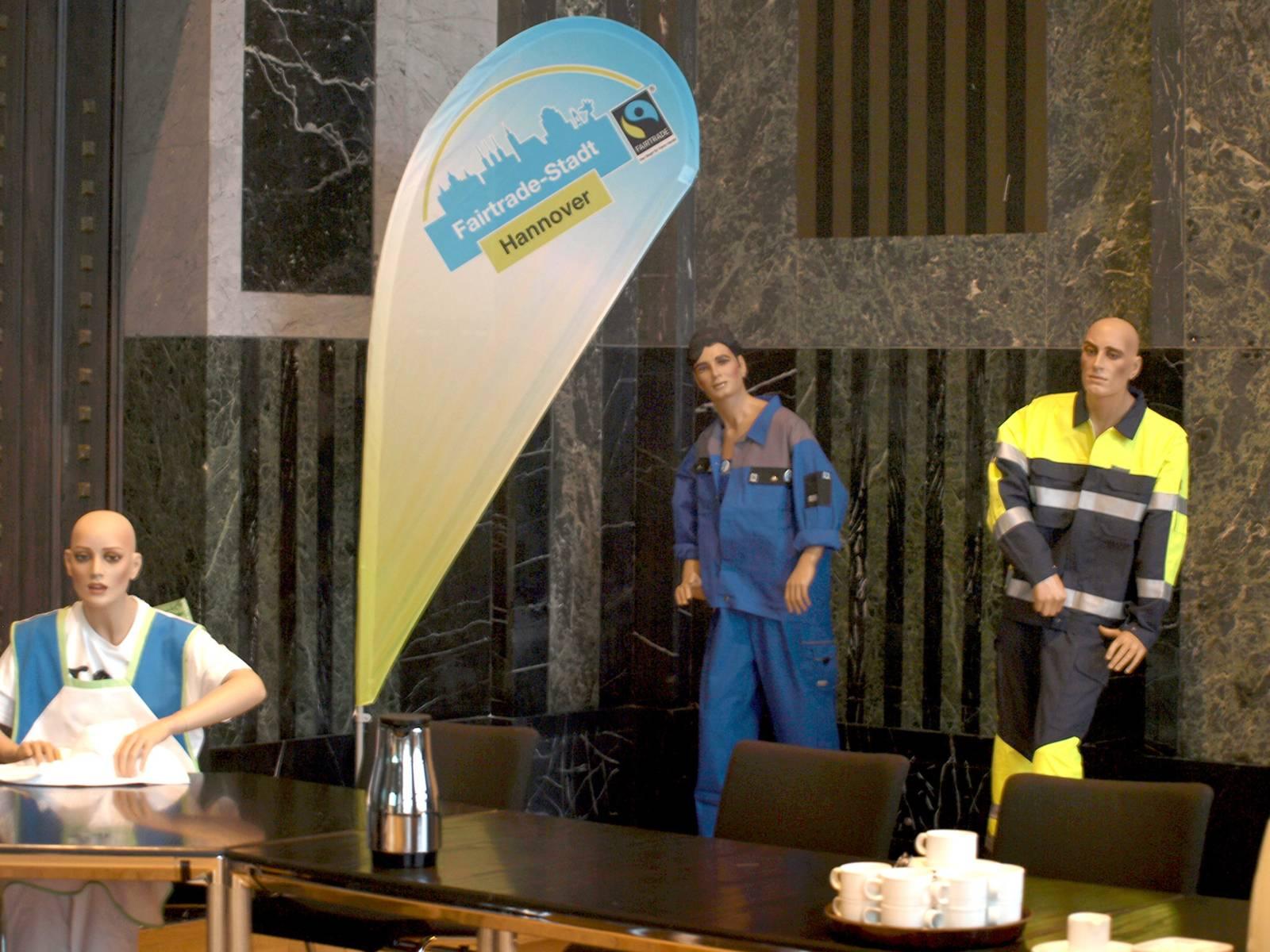 """Drei Schaufensterpuppen sind mit Arbeitskleidung an und hinter einem Tisch zu sehen, daneben eine Fahne mit der Aufschrift """"Fairtrade-Stadt Hannover"""""""