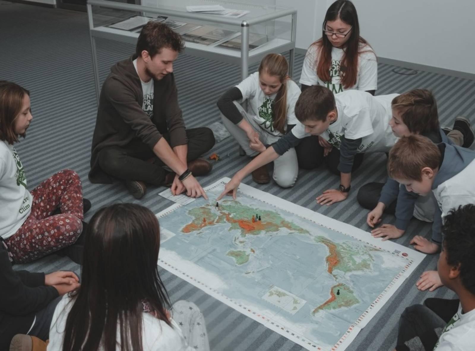 Kinder sitzen beim Weltspiel um eine große Weltkarte
