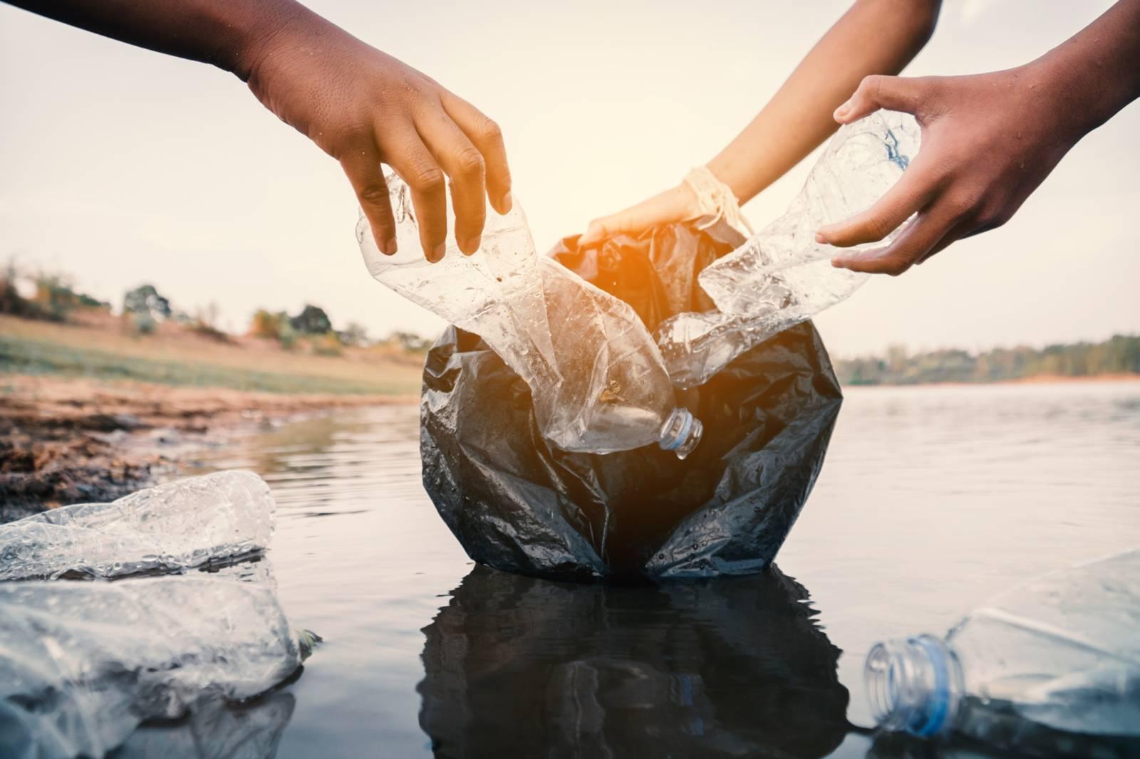 Zwei Menschen, die Plastikflaschen aus dem Wasser ziehen.