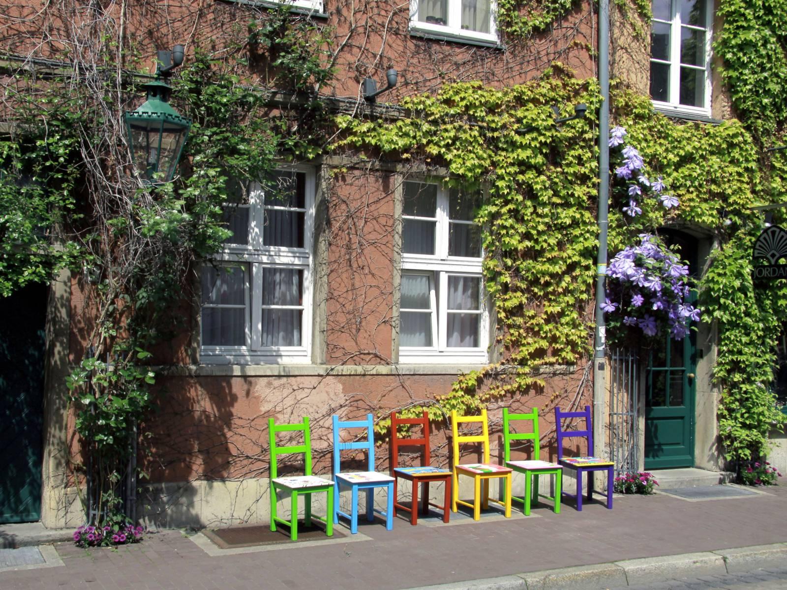 Bunte Stühle auf einer Straße.