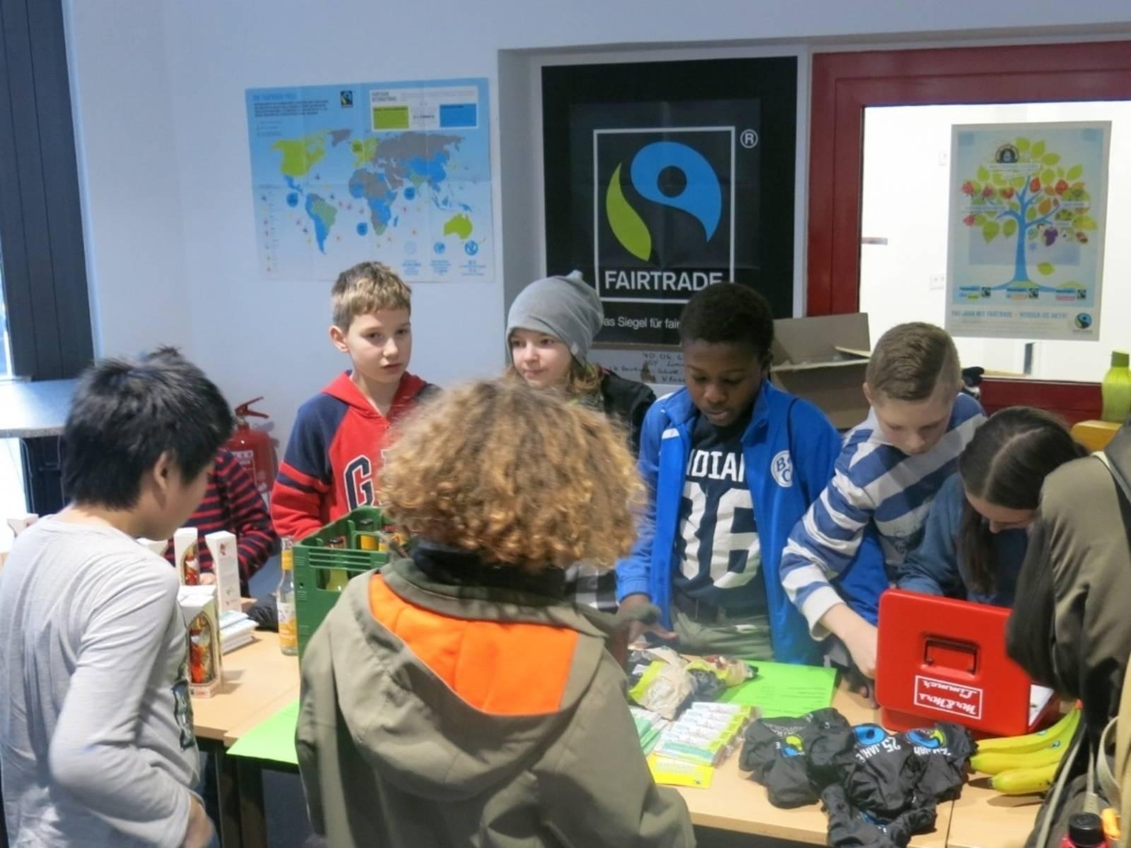 An einer Tischreihe bieten Schülerinnen und Schüler fair gehandelte Produkte an.