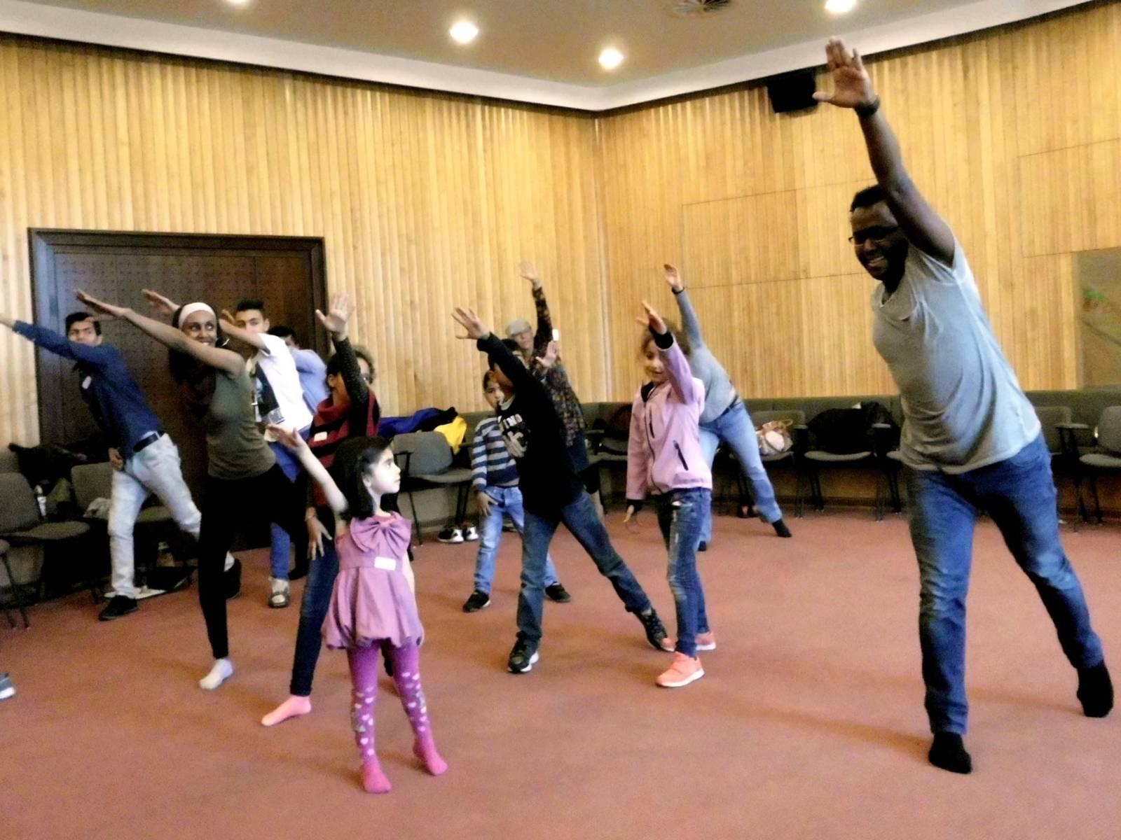 Kinder und Erwachsene beim Tanzen.