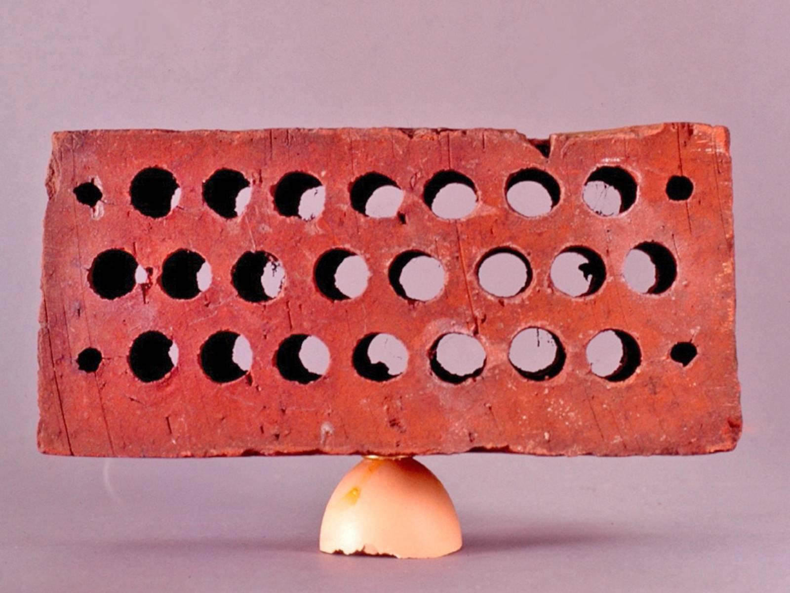 Backstein liegt auf einer umgedrehten halben Eierschale