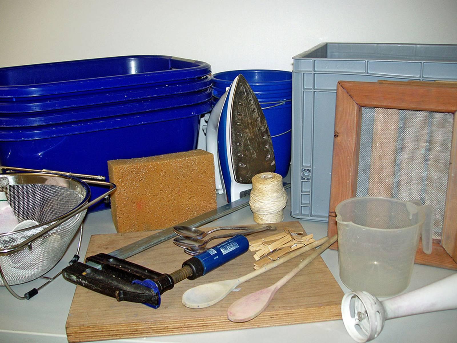 Utensilien fürs Papierschöpfen, die auf einem Tisch ausgebreitet sind: Plastikwannen, Eimer, Zwinge, Schwamm, Siebe, Löffel, Bügeleisen, Wäscheklammern, Leine
