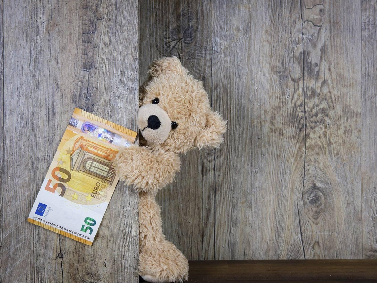 Ein Teddybär lugt hinter einer Holzwand hervor mit einem 50-Euro-Schein in der Hand.