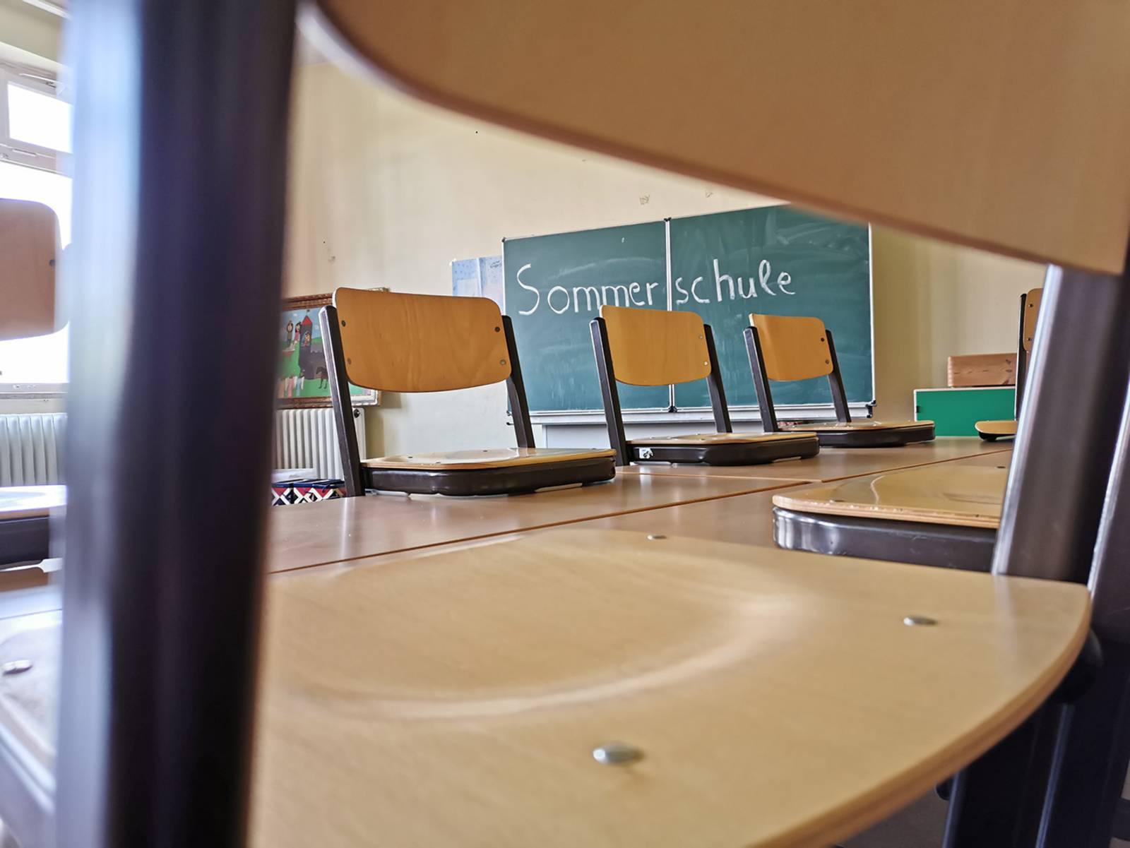 """Tafel in leerem Klassenraum mit der Aufschrift """"Sommerschule"""""""