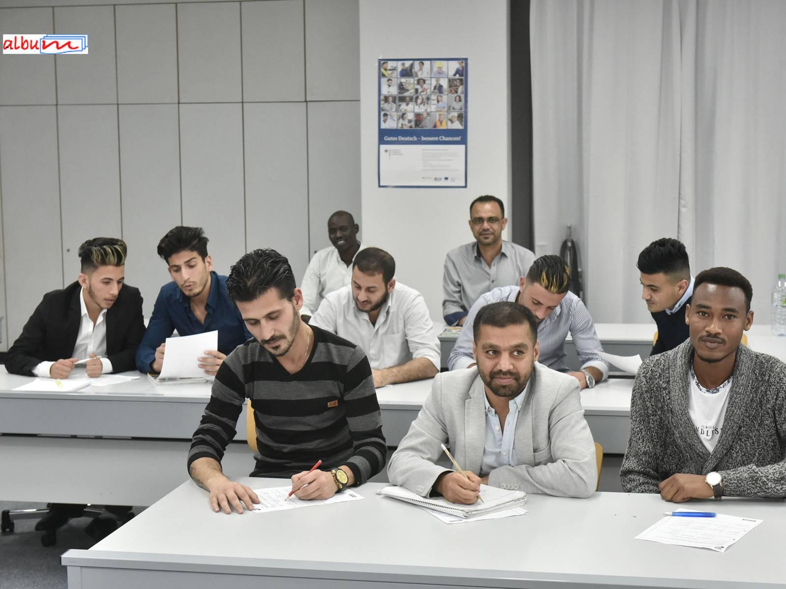 Zehn junge Männer sitzen an Tischen in einem Unterrichtsraum und lösen Aufgaben.