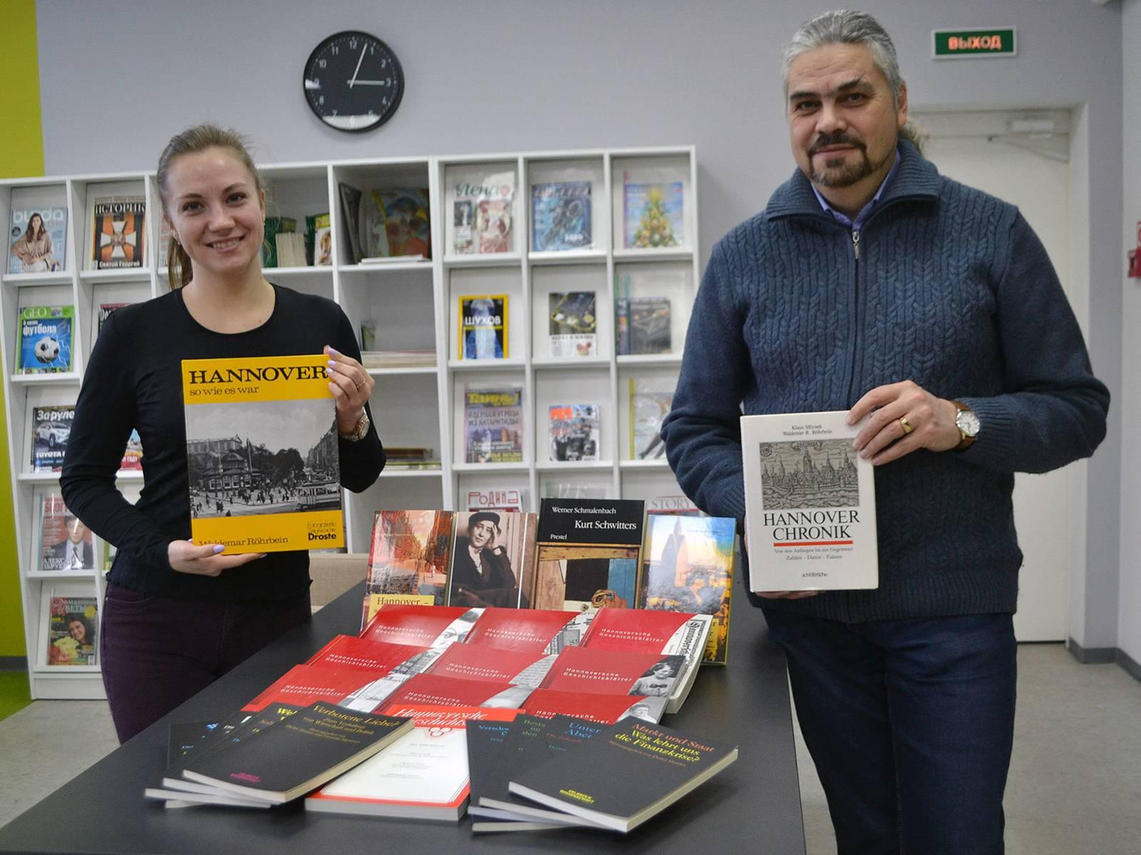Eine Frau und ein Mann posieren in einer Bibliothek für die Kamera und halten jeweils ein Buch über Hannover hoch.