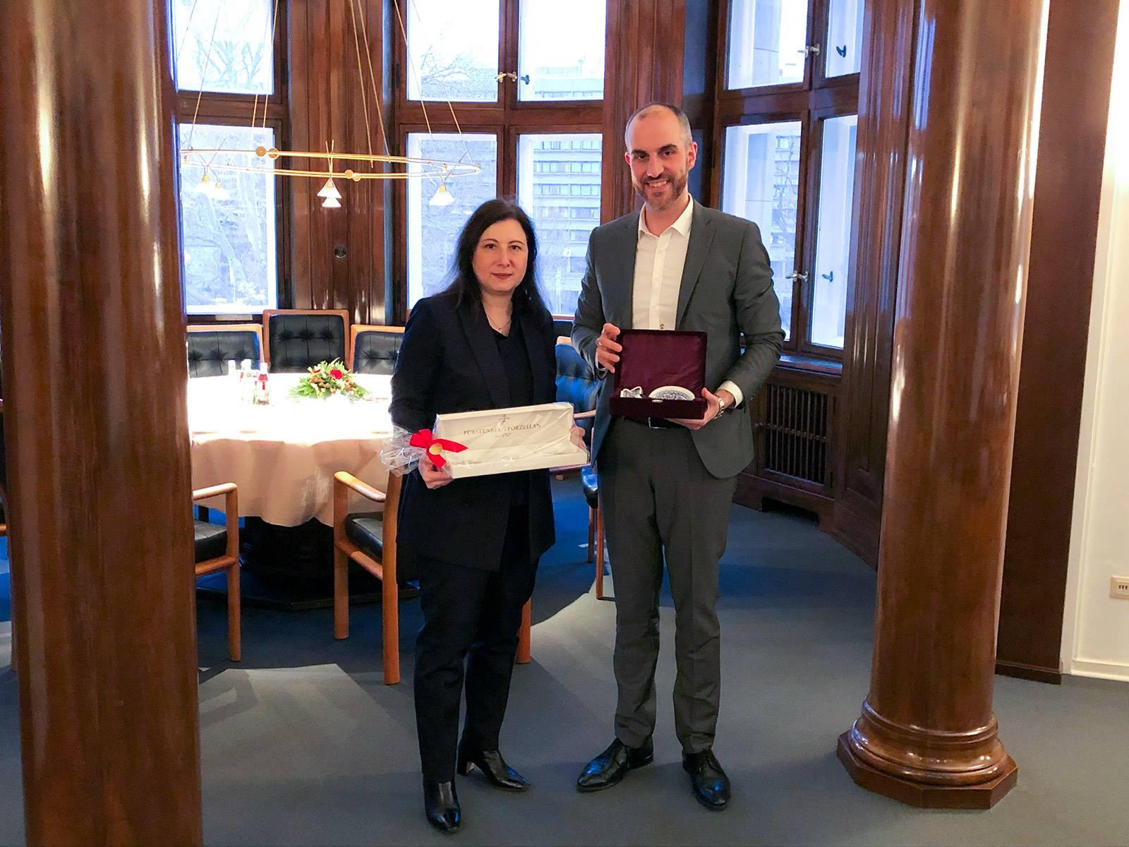 Die türkische Generalkonsulin Banu Malaman und Hannovers Oberbürgermeister Belit Onay posieren vor einem gedeckten Tisch mit Presenten in den Händen.