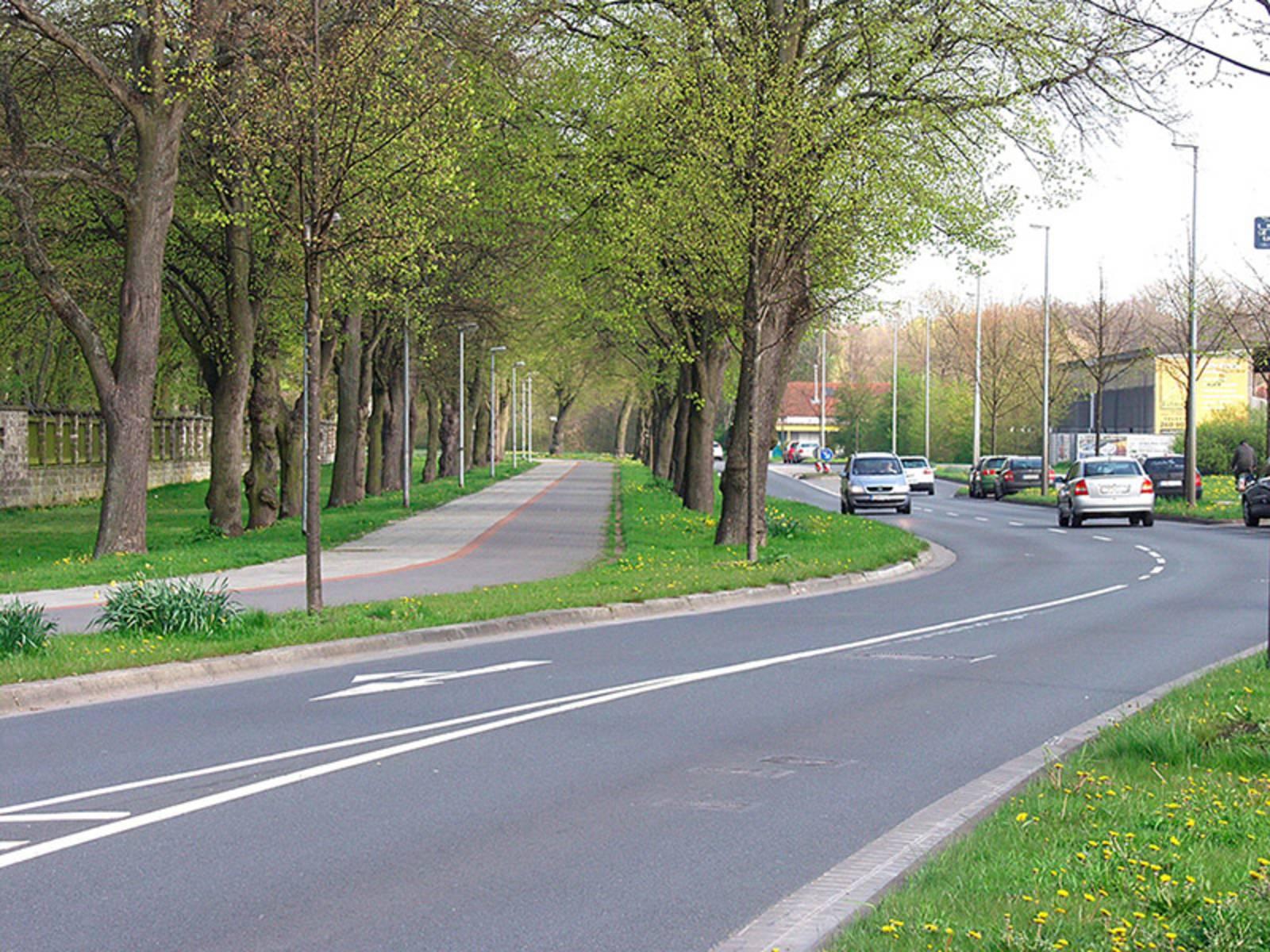 Autos fahren auf einer erneuerten Fahrbahn. Daneben ein sanierter Fahrrad- und Fußgängerweg.