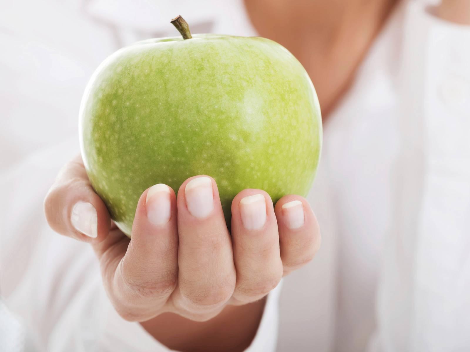Ein grüner Apfel wird von einer Hand umschlossen