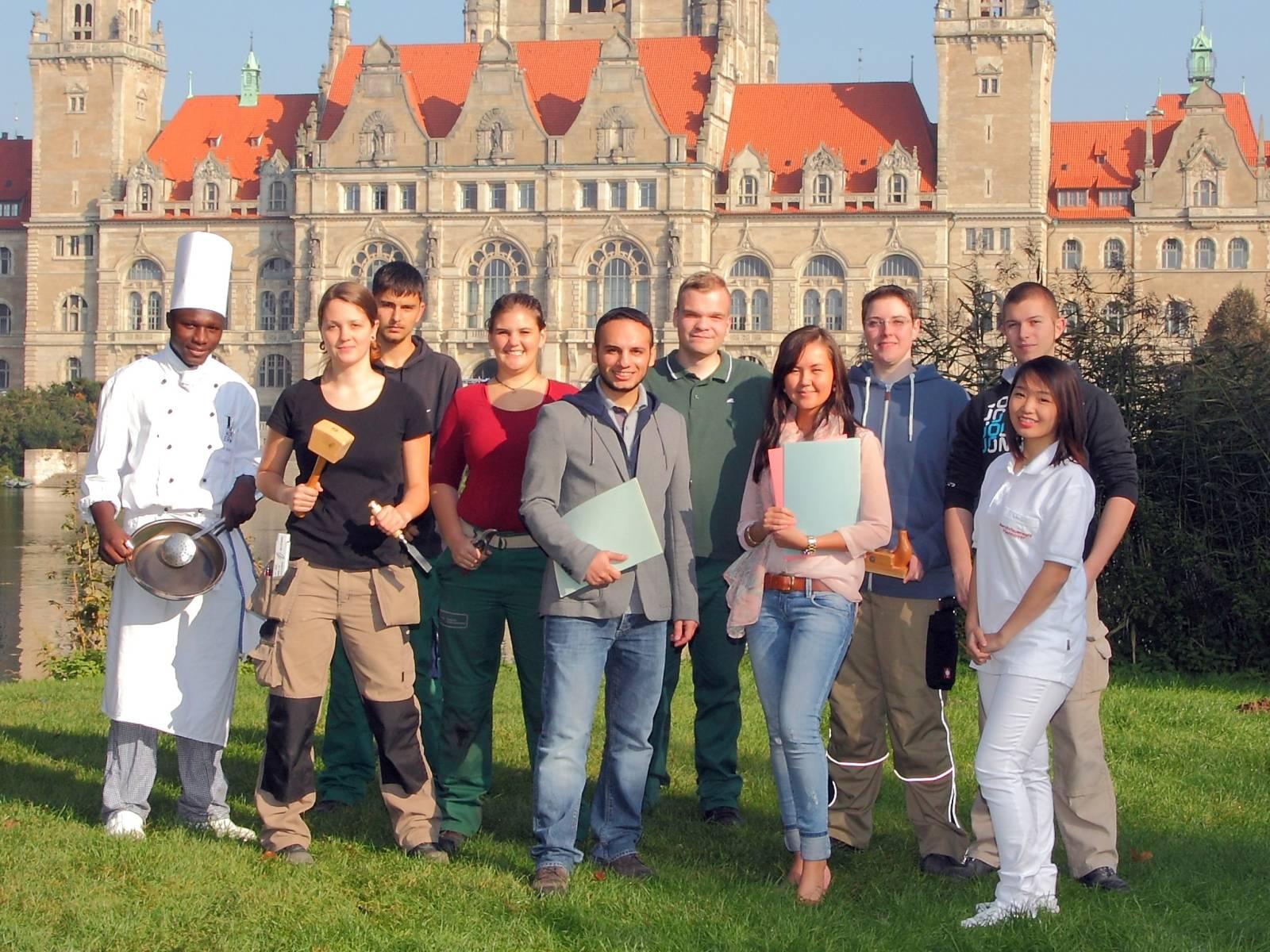 Zehn Auszubildende - zum Teil in Berufsbekleidung - vor dem Hannoverschen Rathaus