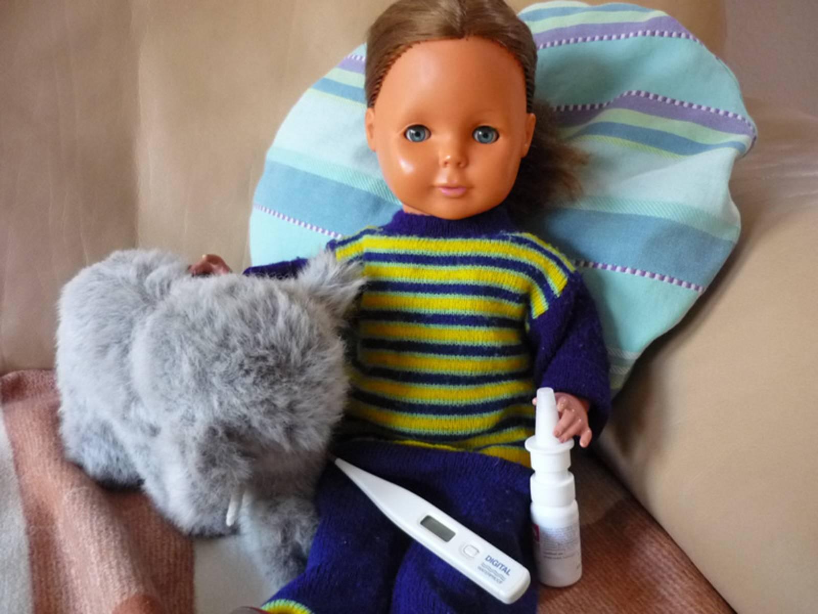 Puppe und Stofftier mit Fieberthermometer und Schnupfenspray