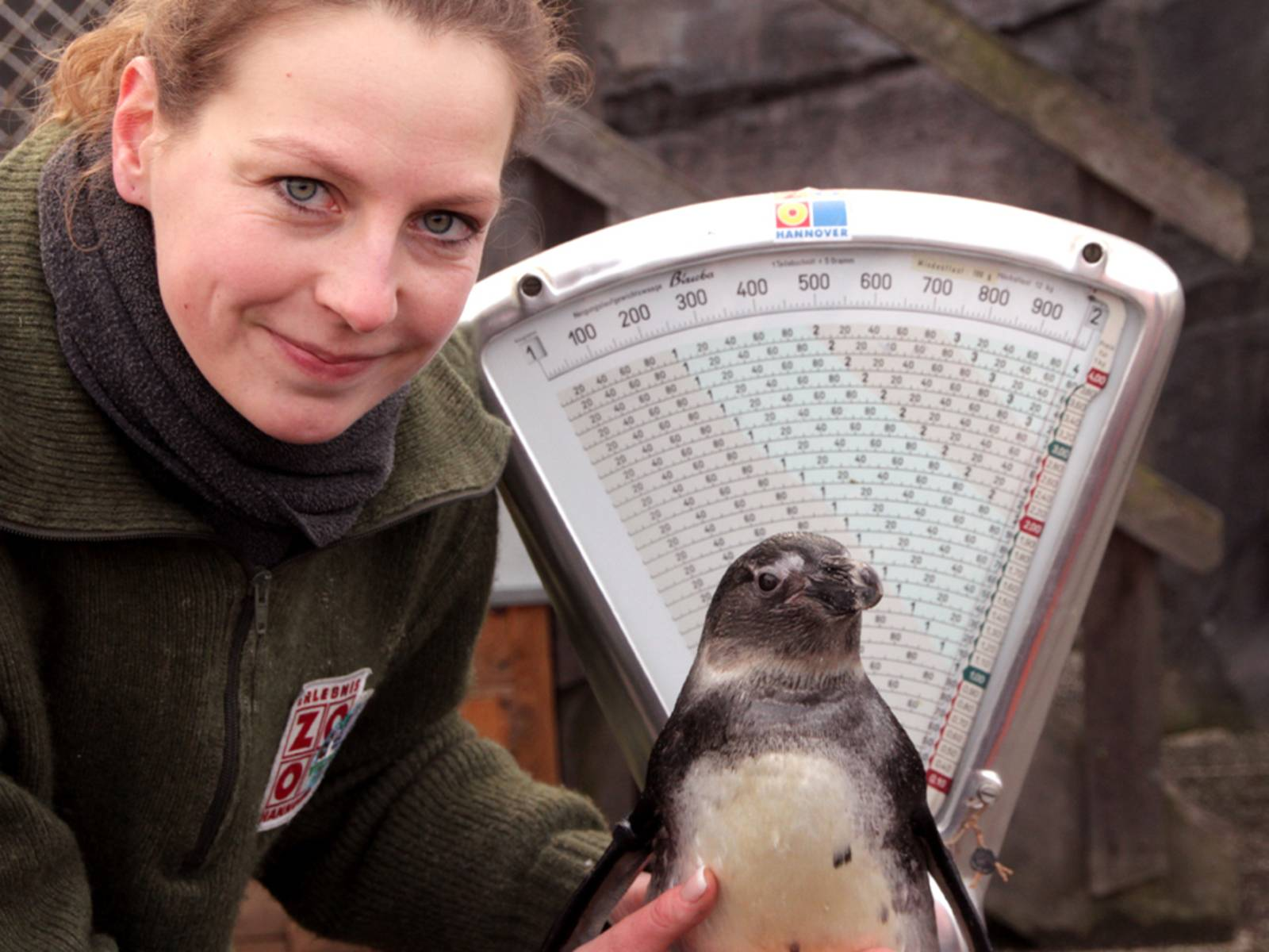 Frau mit Pinguin vor Waage.