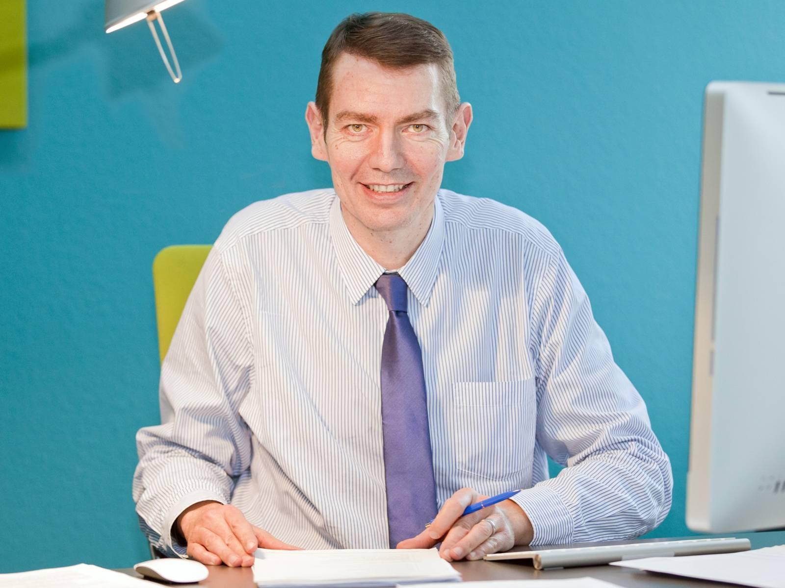 Mann in Hemd und Krarwatte sitzt an einem Schreibtisch.