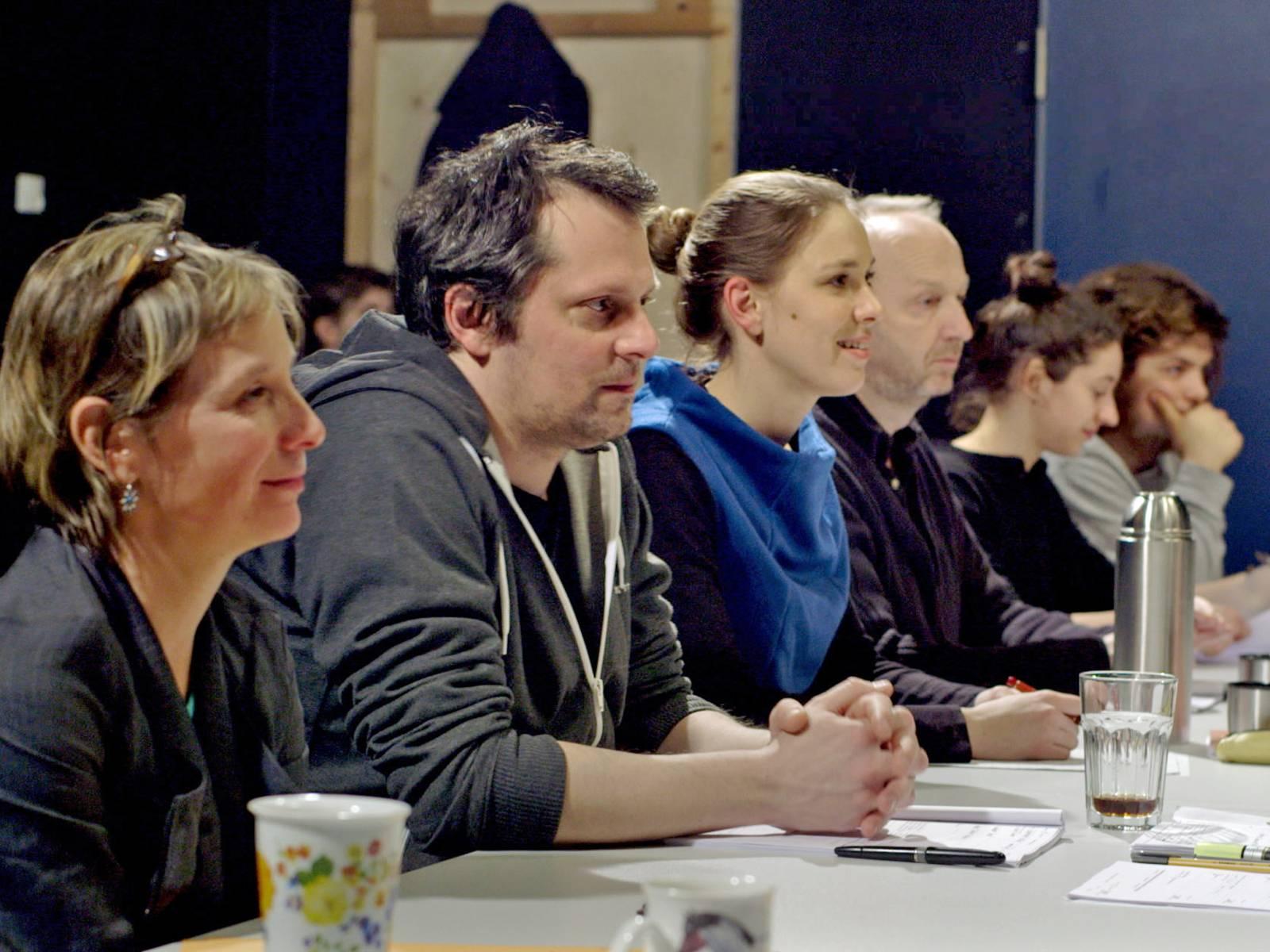 Die Prüfer der Hochschule für Musik, Theater und Medien Hannover sitzen nebeneinander an einem langen Tisch.