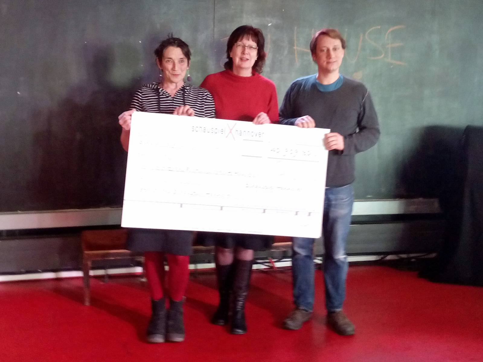 Zwei Frauen und ein Mann mit einem großen Scheck.