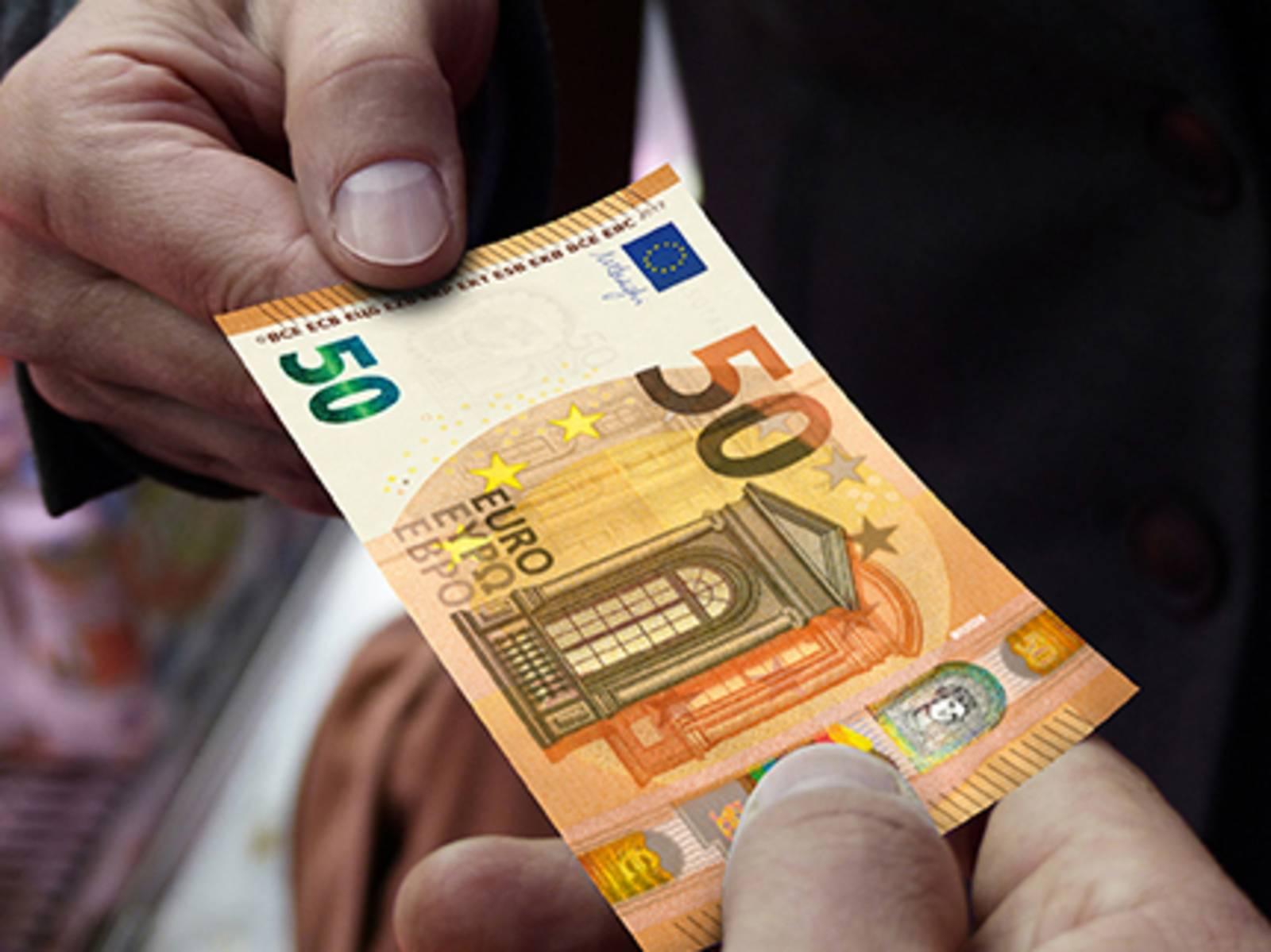 Ein Geldschein wird weitergereicht.