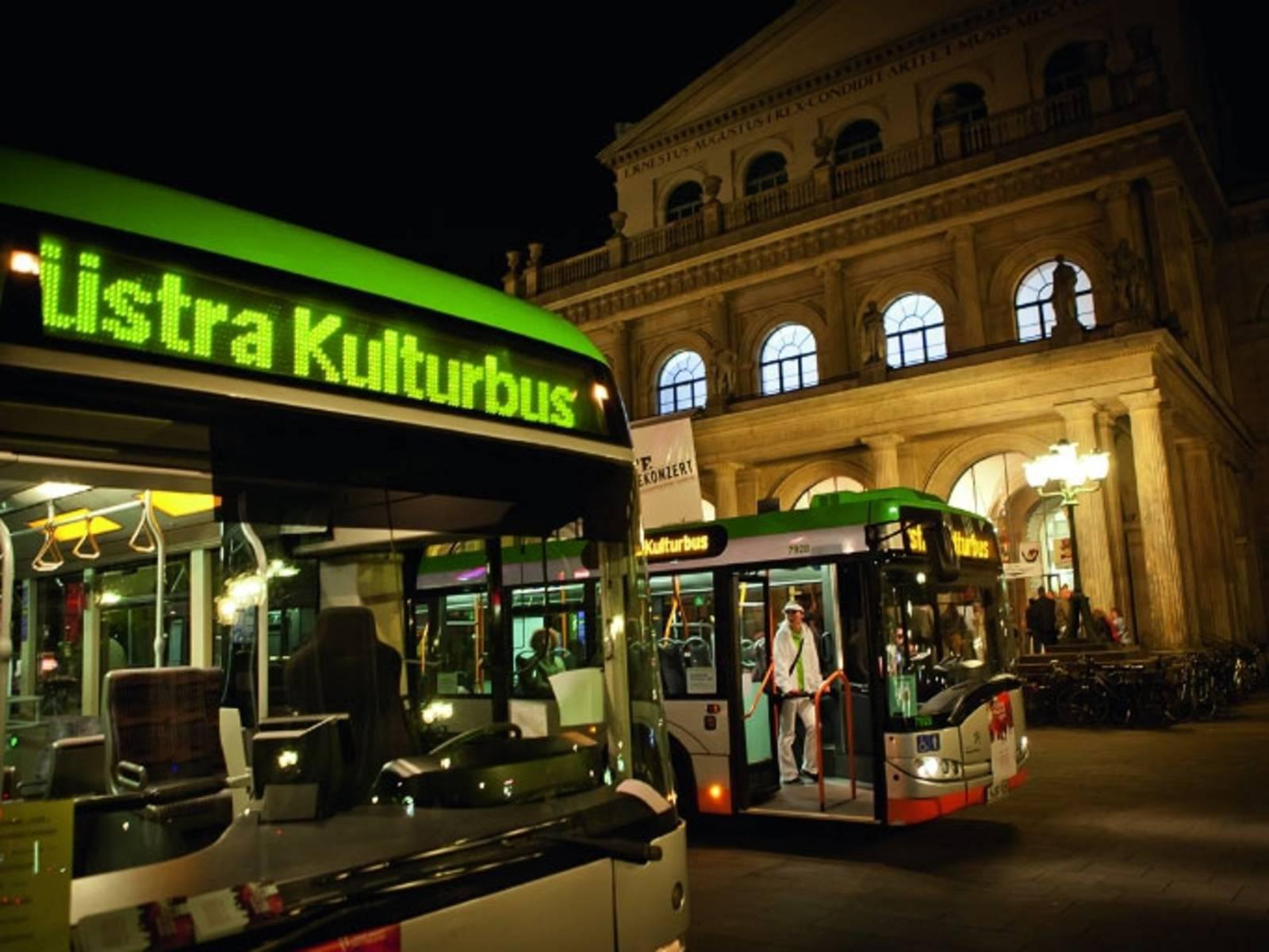 Zwei Busse stehen vor einem Opernhaus.