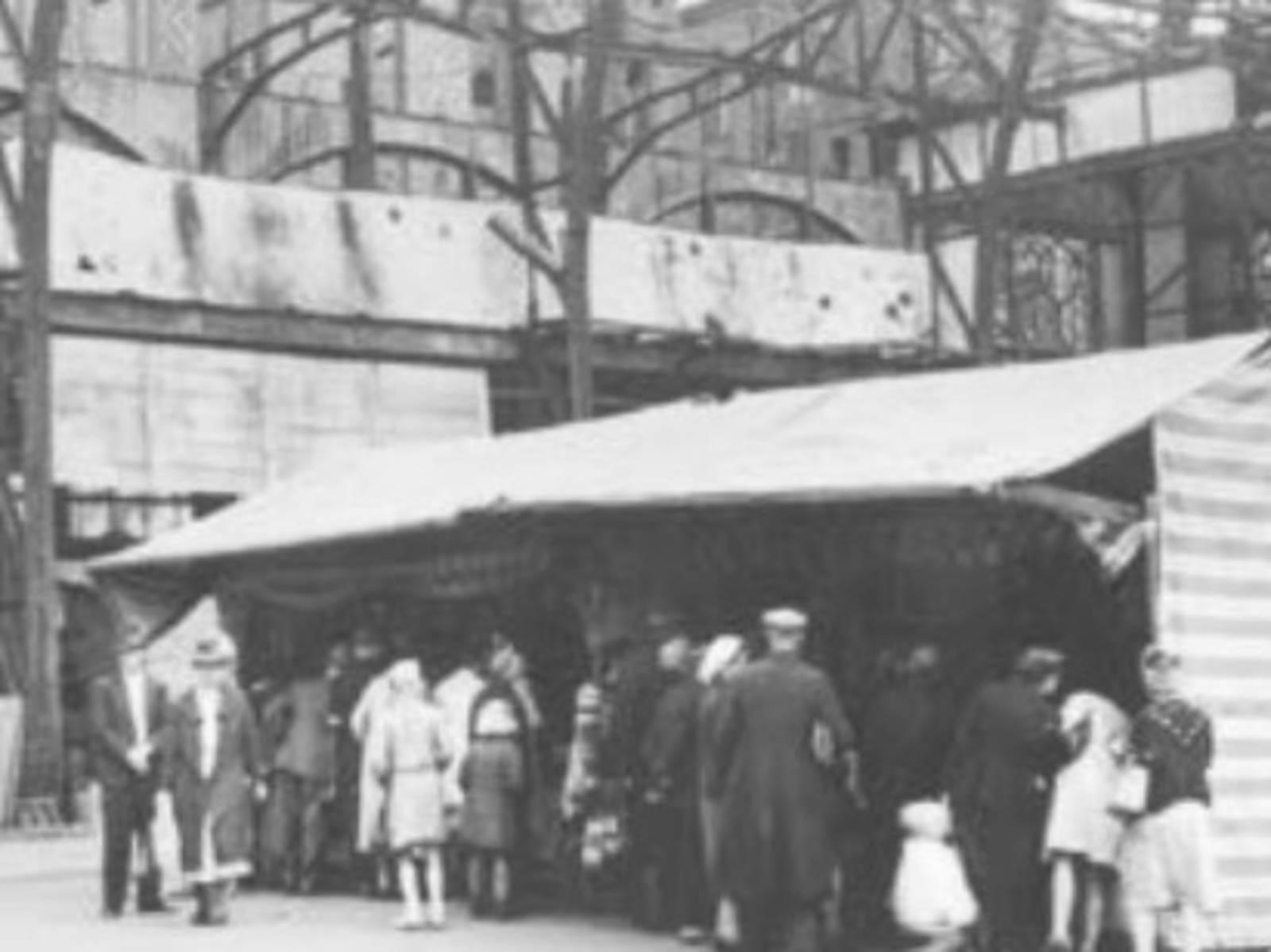 Verkaufsbude aus Holz in Trümmern eines zerstörten großen Gebäudes