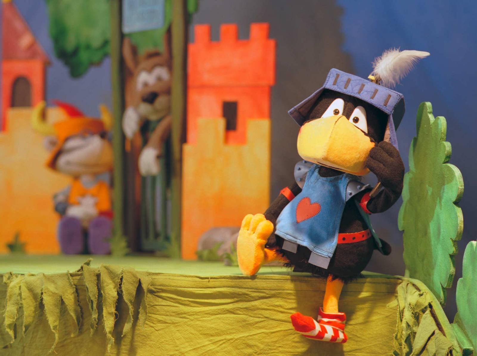 Szene aus einem Stück: Ein Rabe im Ritterkostüm sitzt vor einer Burg.