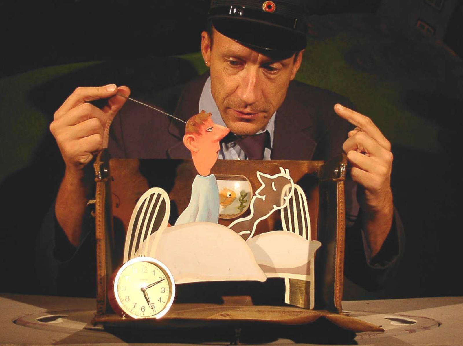Achim Fuchs-Bortfeldt vom Figurentheater Die Füchse steht hinter einen kleinen Bühne und spielt mit einer Pappfigur, die sich aus ihrem Bett erhebt.