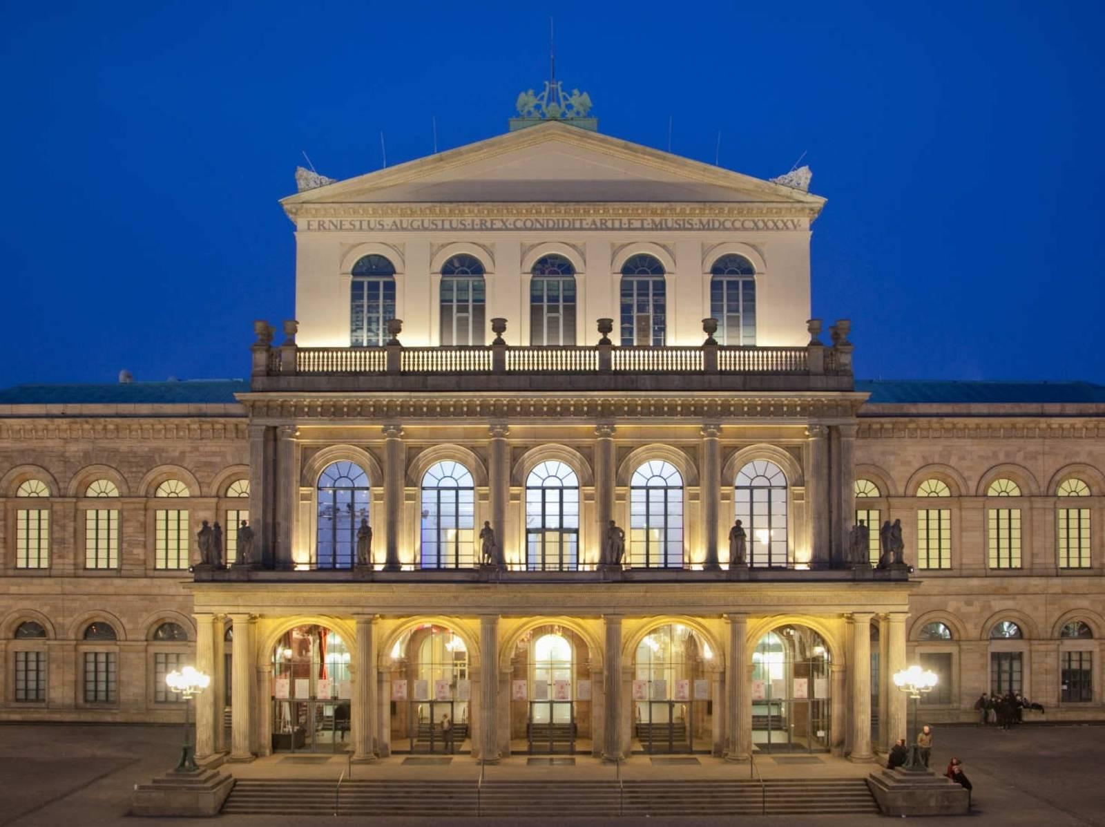 Das erleuchtete Opernhaus in der Frontansicht bei Nacht.