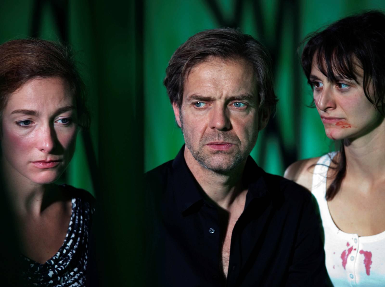 Szene aus einem Stück: Zwei Frauen und ein Mann schauen ernst, die eine Frau hat Blut im Gesicht und an ihrem T-Shirt.