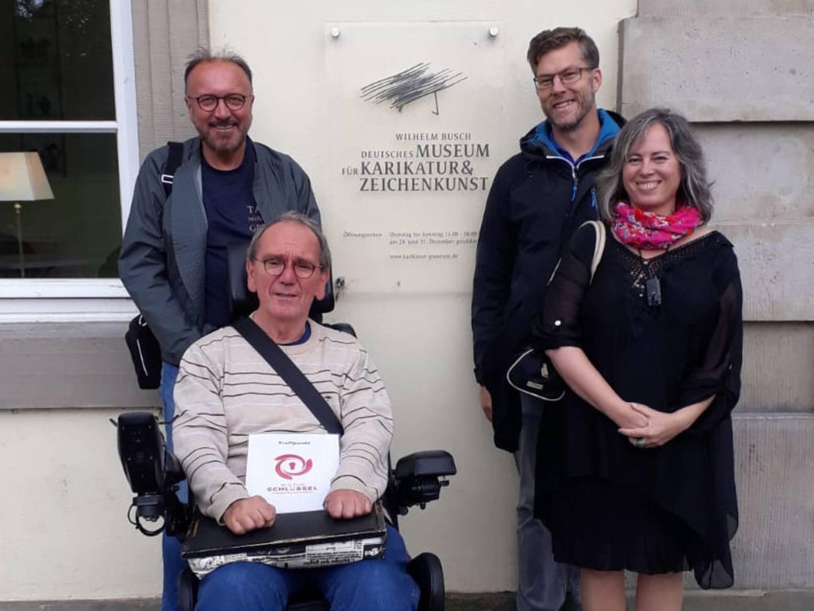 Drei Männer und eine Frau stehen vor einem Gebäude. Einer der Männer sitzt in einem Rollstuhl.
