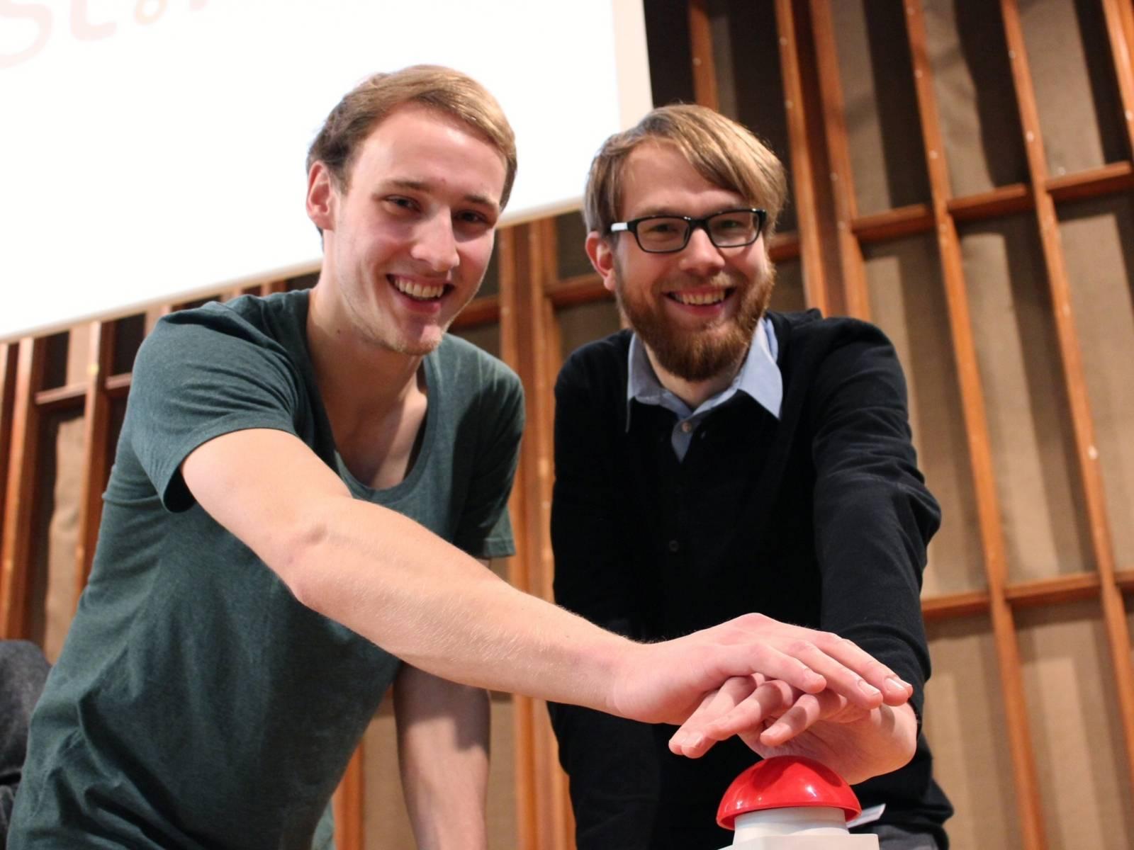 Zwei junge Männer drücken auf einen großen roten Startknopf