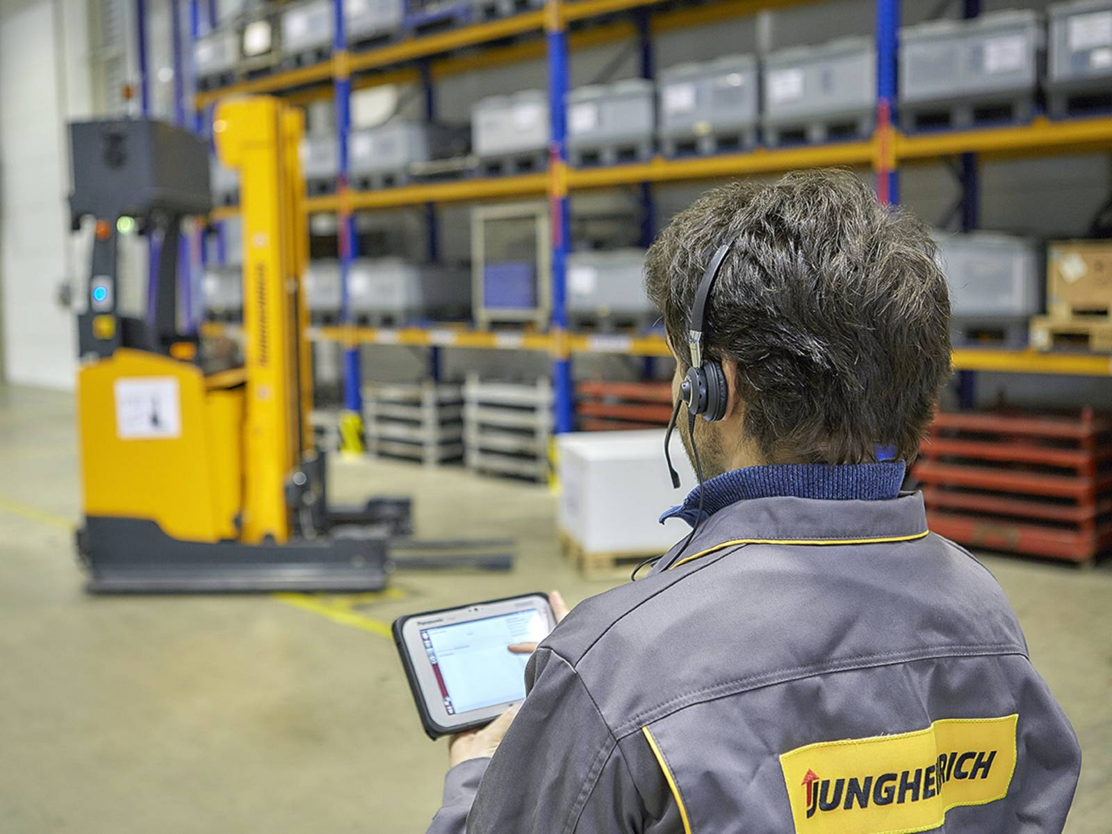 Foto: Ein Mann steuert mit Tablet und Headset einen intelligenten Schubmaststapler.