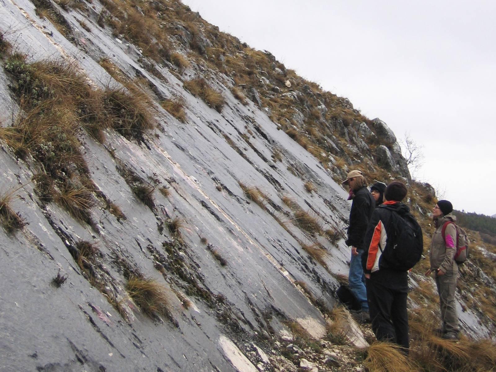 Mehrere Menschen in wetterfester Kleidung an einem Berghang