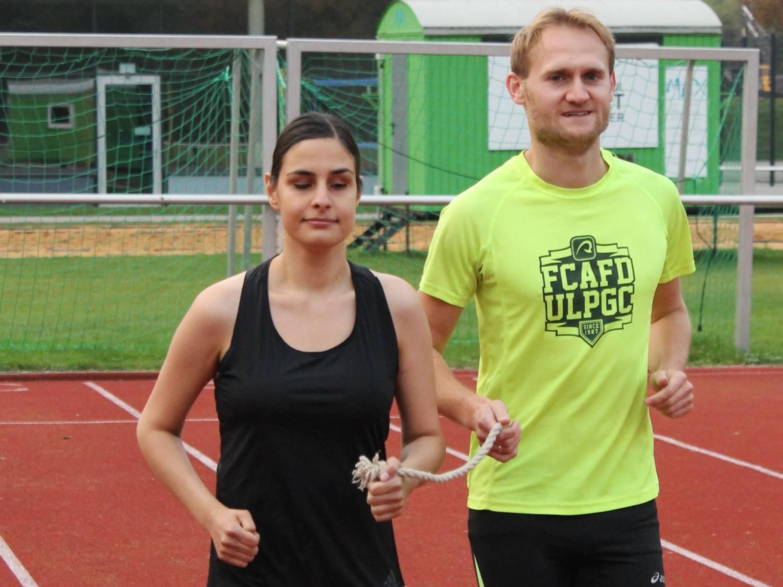 Eine Frau und ein Mann beim Laufen, beide halten ein Seil in den Händen.