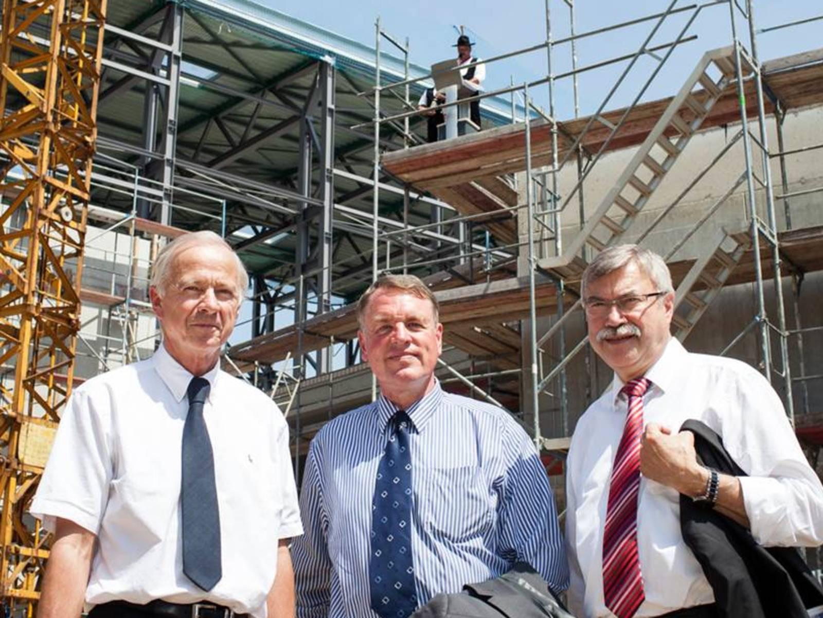 Drei Männer vor einem Rohbau