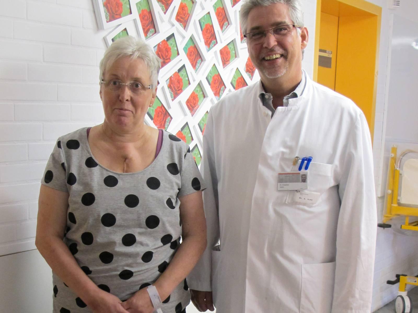 Ein Mann in weißem Kittel und eine Frau stehen in einem Krankenhausflur