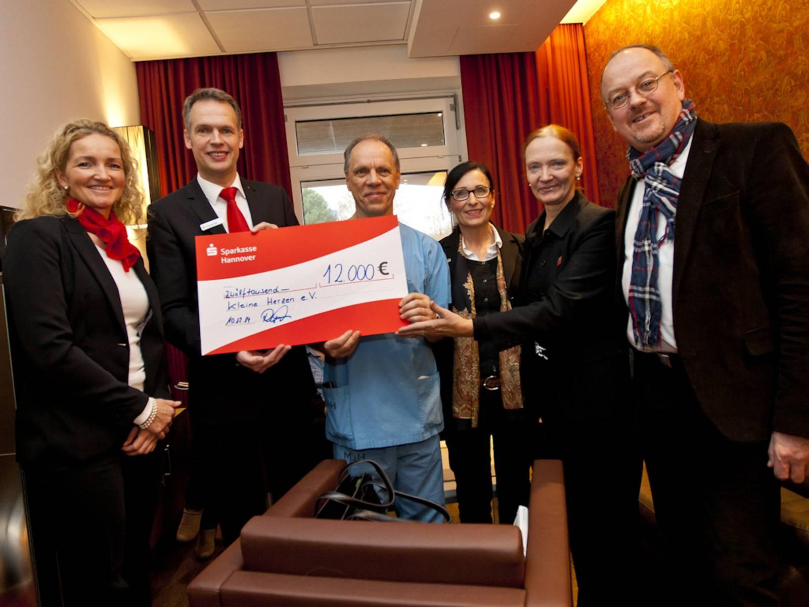 Drei Frauen und drei Männer halten einen symbolischen rot-weißen Check über 12.000 € in die Kamera.