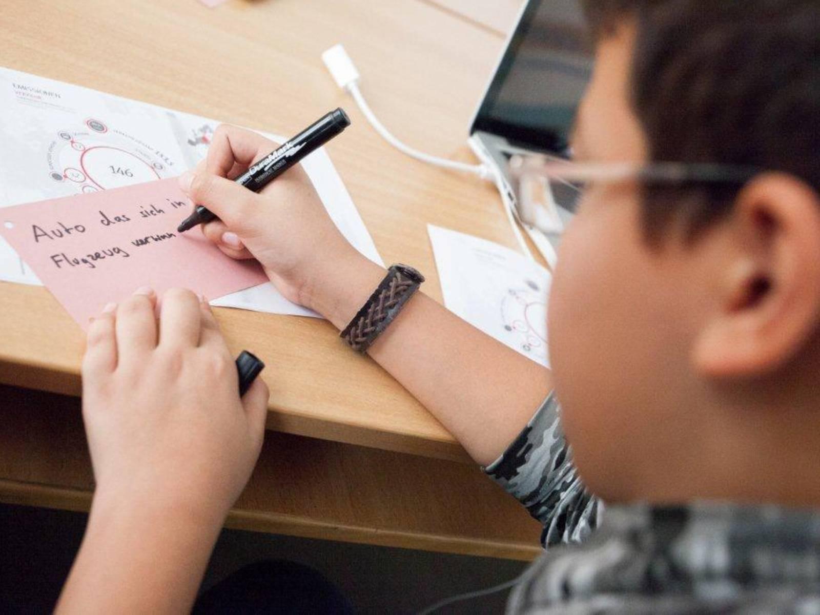 Eine Junge schreibt etwas auf ein Stück Papier.