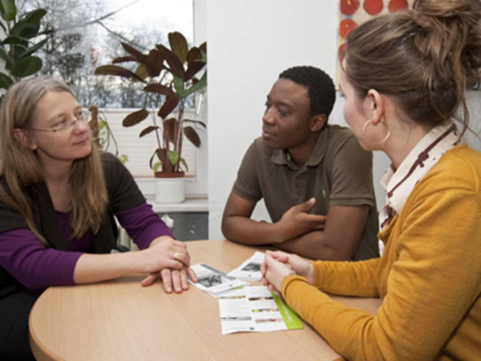 Eine Frau berät zwei junge Erwachsene.
