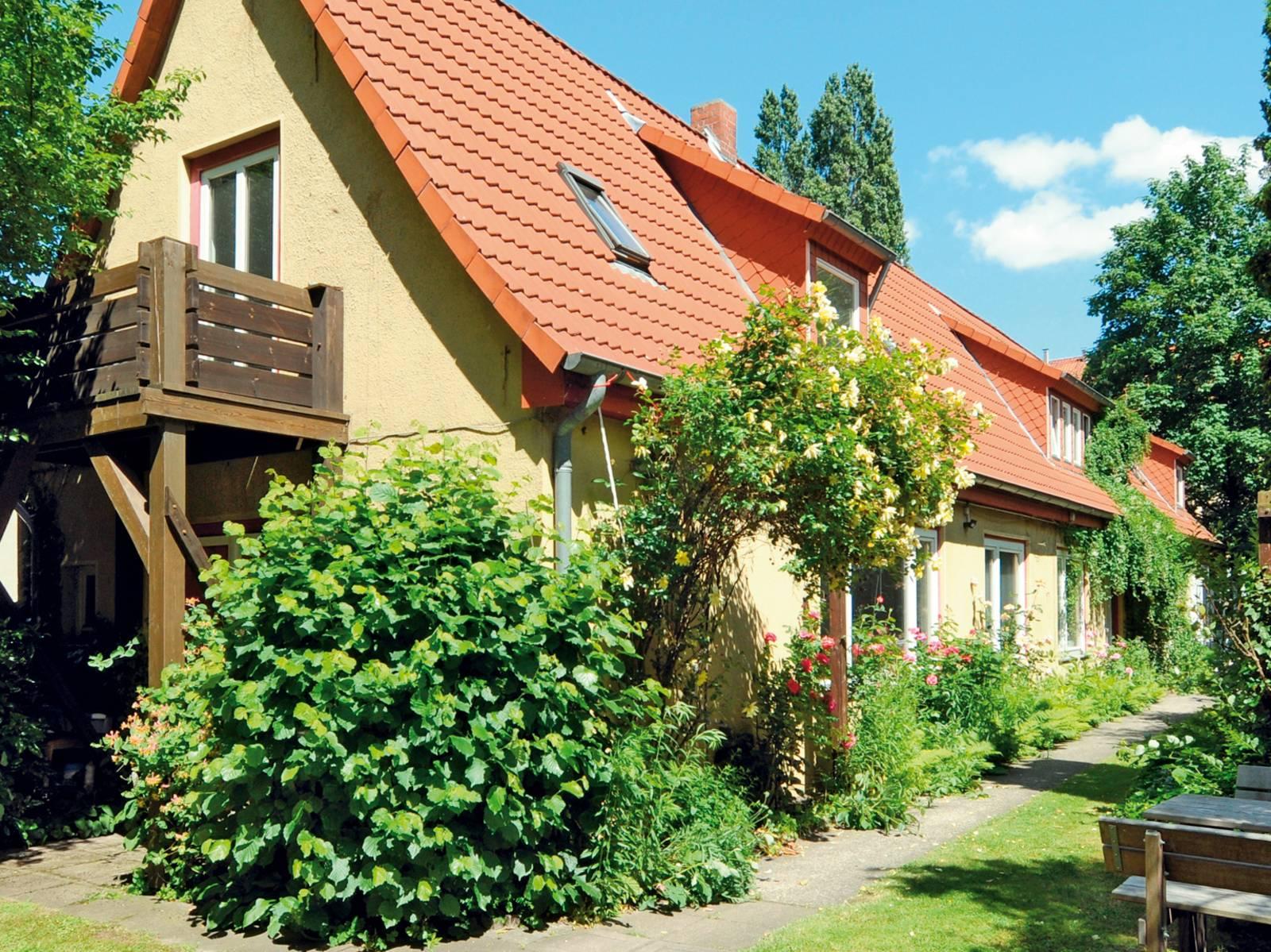 Haus mit Holzbalkon, umgeben von Bäumen und Büschen.