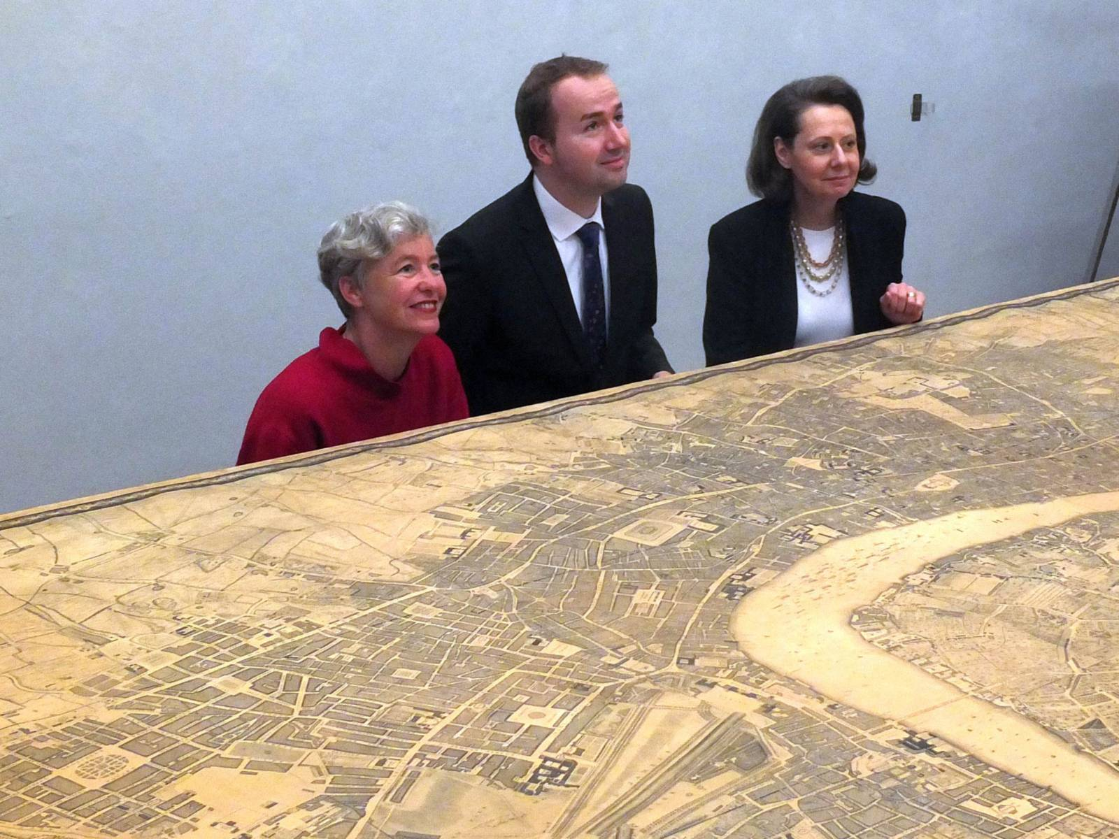Ein Mann und eine Frau hinter einem 4 Meter breiten historischen Stadtplan von London.