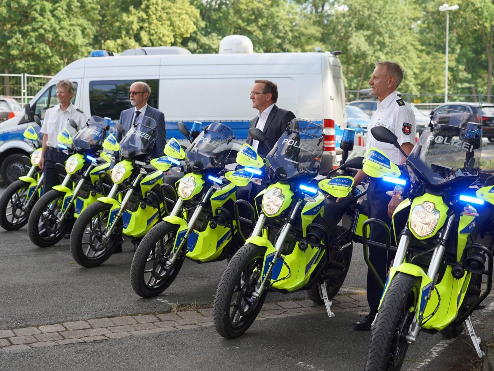 Polizisten stehen neben Motorrädern
