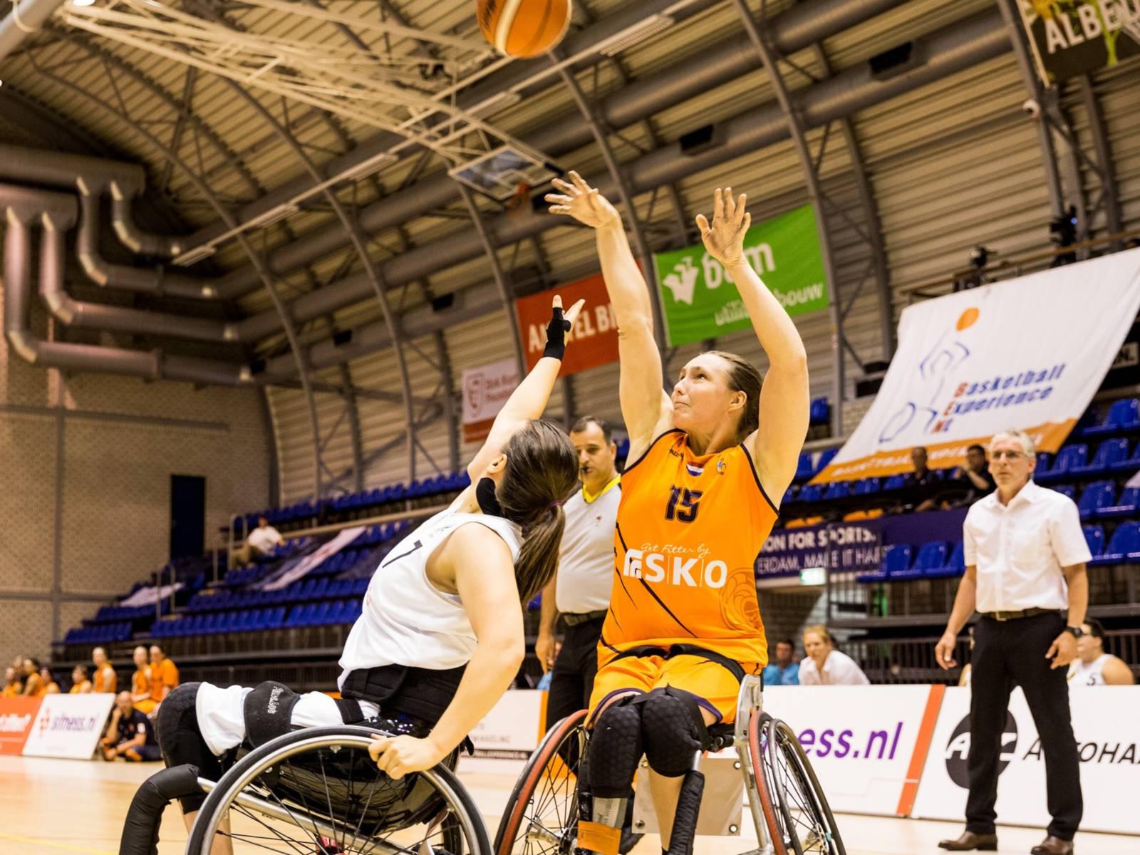 Zwei Frauen in Rollstühlen spielen Basketball