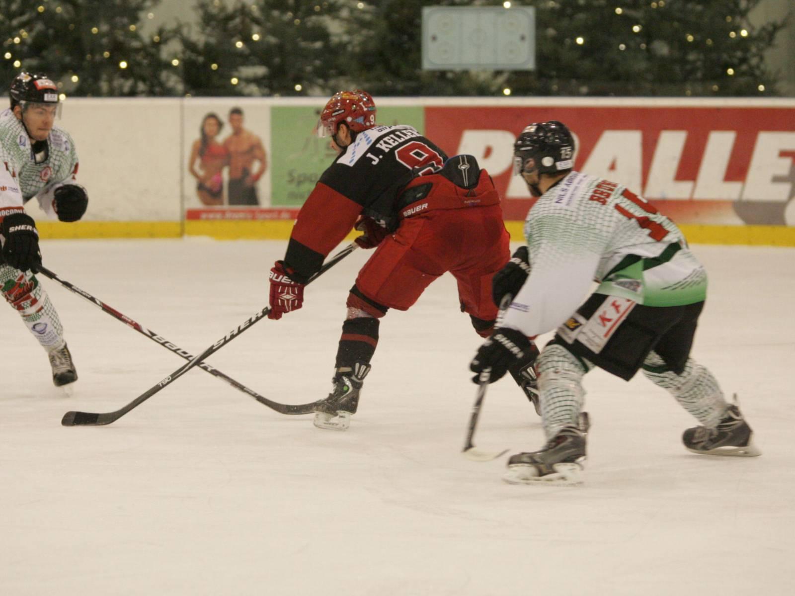 Drei Eishockeyspieler kämpfen um den Puck.